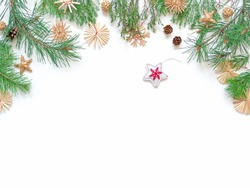 Christmas composition. Fabric star, straw decorations, pine cone are on a white background. The mockup is framed by sprigs of coniferous plants. New Year concept. Flat lay. Top view. Copy space.