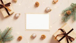Christmas composition. Feminine table with blank paper card mockup, gift boxes, fir tree branches, balls, garland on pastel beige background. Flat lay, top view. Nordic, hygge, cozy Xmas concept
