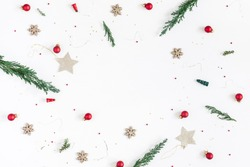 Christmas composition. Frame made of christmas tree branches, golden decorations and red berries on white background. Flat lay, top view, copy space