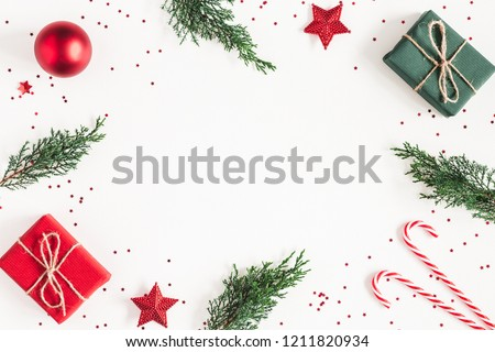 Christmas composition. Frame made of gifts, fir tree branches, red decorations on white background. Christmas, winter, new year concept. Flat lay, top view, copy space #1211820934