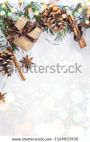 Christmas composition. Gift box, ribbon, fir branches, cones, anise, cinnamon on white background. Flat lay, top view, mock up copy space vertical