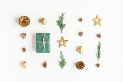 Christmas composition. Gift, christmas golden decorations, cypress branches, pine cones on white background. Flat lay, top view