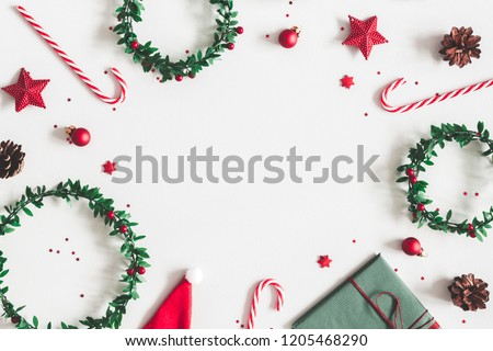 Christmas composition. Gift, wreaths, red decorations on pastel gray background. Christmas, winter, new year concept. Flat lay, top view, copy space #1205468290