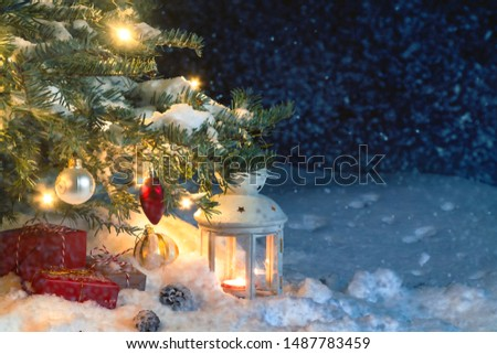 Christmas composition - gifts and a lantern in the snow under a Christmas tree decorated with lights and Christmas-tree decorations, copy space, place for text
