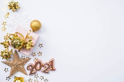 Christmas composition. Gifts, stars, gold jewelry and the number 2021 on a white background. Christmas, winter, new year concept. Flat lay, top view, copy space.