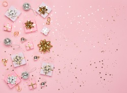 Christmas composition. Gold and silver decorations, mirror disco balls, gifts on pastel pink paper background. Christmas, winter, new year concept. Flat lay, top view, copy space.