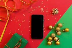 Christmas composition. Green gift box, mobile phone on red and green background with golden confetti. new year concept. Greeting card, xmas celebration 2020. Flat lay, top view, copy space, mockup