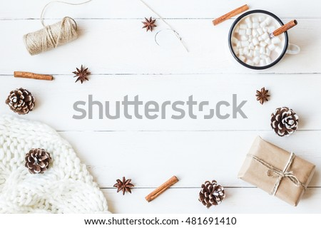 Christmas composition. Hot chocolate, cinnamon sticks, anise star, marshmallow, knitted blanket, christmas gift and cones. Winter. Flat lay, top view