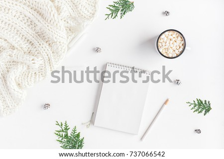 Christmas composition. Hot chocolate, knitted blanket, notebook, thuja branches on white background. Christmas, winter, new year concept. Flat lay, top view, copy space
