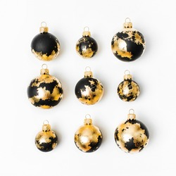 Christmas composition made of black Christmas balls with gold leaf  on white background. Flat lay, top view