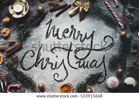 Christmas composition. Merry christmas text made with flour on black background, snow, december, top view, flat lay