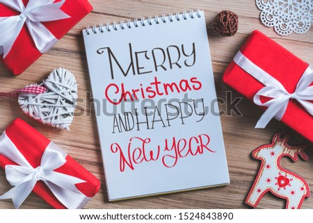 Christmas composition of pine tree decorations and gift boxes with open notebook wish hand drawn best wishes. Top view, flat lay.