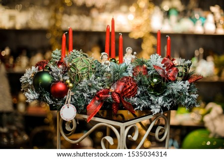 Christmas composition of snow covered fir-tree branches, candles, tapes, red and green toy balls and toy children in the blurred background of flower shop #1535034314