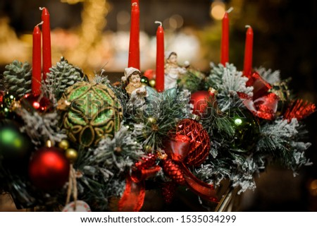 Christmas composition of snow covered fir-tree, candles, tapes, red and green toy balls and toy children in the blurred background of flower shop #1535034299