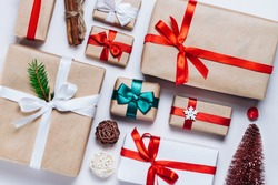 Christmas composition of various gift boxes wrapped in craft and white paper and decorated with satin red ribbons. Top view, flat lay. White background.