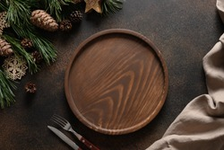 Christmas composition of wooden tray for holiday homemade dish on brown cozy home table with natural decoration. Top view.