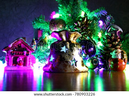 Christmas composition. On the background of green branches of trees laid out toys, balls, Santa Claus, the house and the bag candle holder, candle burning inside, big shot, included garland, shooting #780903226
