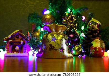 Christmas composition. On the background of green branches of trees laid out toys, balls, Santa Claus, the house and the bag candle holder, candle burning inside, big shot, included garland, shooting #780903229