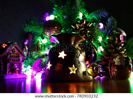Christmas composition. On the background of green branches of trees laid out toys, balls, Santa Claus, the house and the bag candle holder, candle burning inside, big shot, included garland, shooting #780903232