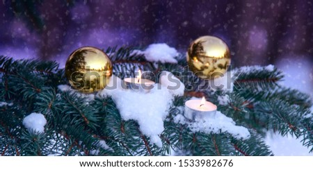 Christmas composition outdoors close up. Two small candles lie on a snowy fir branch next to two golden balls and snow is falling. Blurred background. Banner. #1533982676