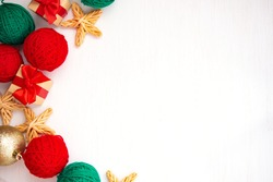 Christmas composition. Red and green balls of yarn, gifts with a red bow on a white background. Bright yarn knitting concept. Flat lay, top view.