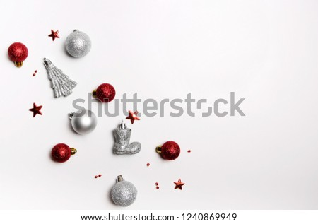 Christmas composition. Red balls, silver balls, Santa's boots and spruce on a white background. Flat lay, top view #1240869949