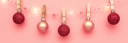 Christmas composition, trendy colors. Banner of shiny christmass garland with hanging by wooden pins pink and red balls over pink background. Christmas, winter, new year concept. Front view
