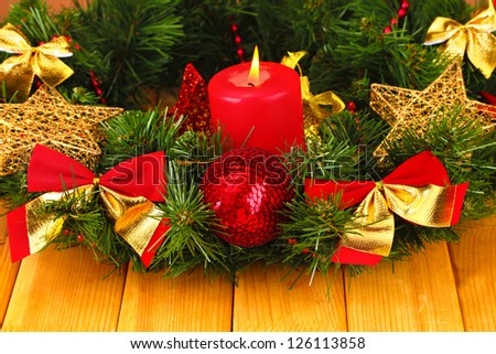 Christmas composition  with candle and decorations in red and gold colors on wooden background
