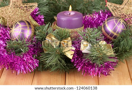 christmas composition with candles and decorations in purple and gold colors on wooden background
