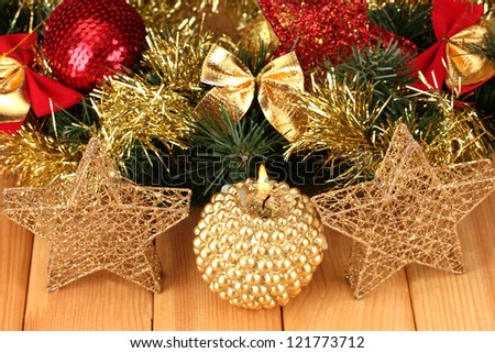 Christmas composition  with candles and decorations in red and gold colors on wooden background