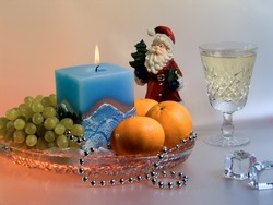 Christmas composition with fruits, candle, Santa Claus and  wineglass.