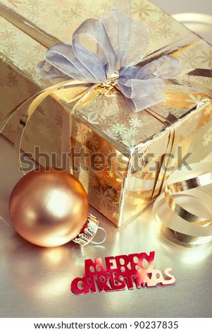 Christmas composition with gift box and bauble, closeup shot, focus on the text