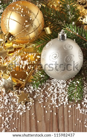Christmas composition with golden and silver baubles on the snow.
