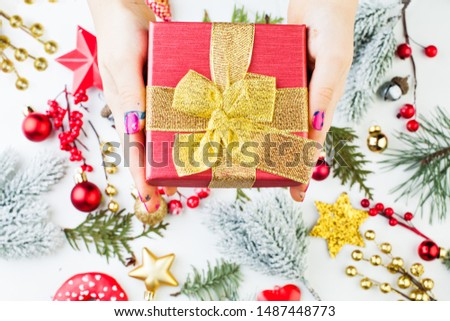 Christmas composition with hand holding gift red gift box with golden ribbon and bow above Xmas decorations background.  Xmas flat lay top view #1487448773