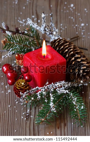 Christmas composition with spruce branch and red candle.