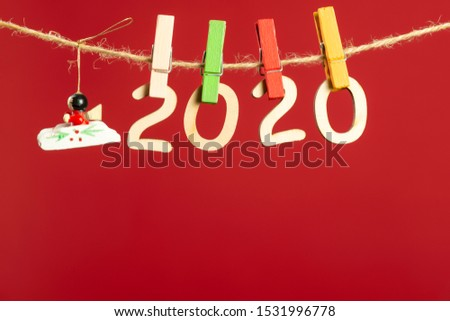 Christmas composition with wooden figures 2020. Figures hang on clothespins on a twine on a red background.