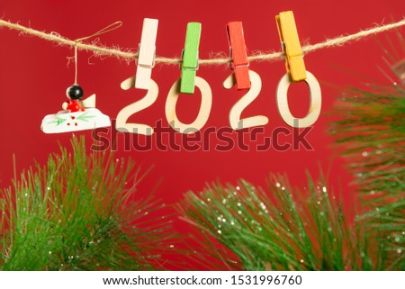 Christmas composition with wooden figures 2020. Figures hang on clothespins on a twine with a Christmas tree branch on a red background. #1531996760
