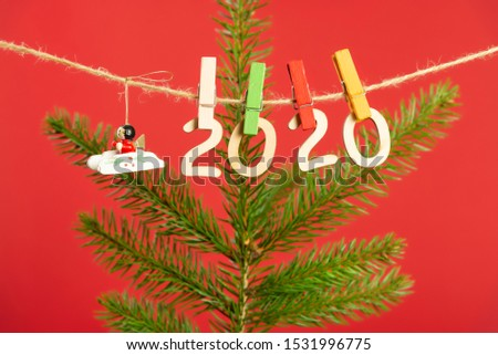 Christmas composition with wooden figures 2020. Figures hang on clothespins on a twine with a Christmas tree branch on a red background.