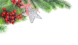 Christmas compositionon with green fir branches, red holly berries and silver star shaped christmas bauble are isolated on a white background, with space for texta white background