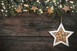Christmas concept background.Christmas tree branches with christmas lights and Christmas star on wood table