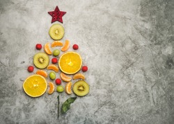 Christmas concept background. Pieces of fruit in the form of a christmas tree on gray background