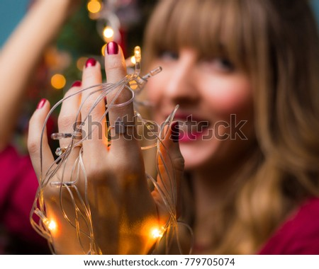Christmas concept. Beautiful girl decorating the Christmas three. Shallow depth of field, selective focus. #779705074