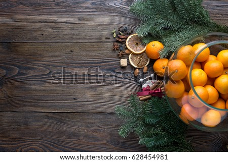 Christmas concept (decoration). Jar with tangerine, cone and walnut on rustic wooden background, top view #628454981