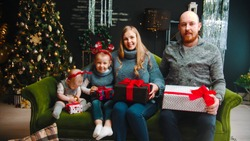 Christmas concept - happu family sitting on the couch holding gifts and looking in the camera