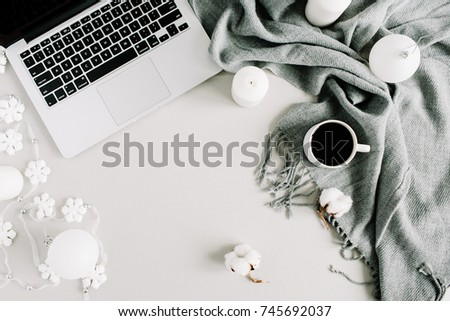 Christmas concept. Home office desk with laptop, plaid, candles, cotton balls and Christmas baubles. Flat lay, top view holiday composition.