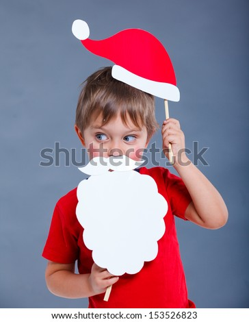 Christmas concept. Smiling funny boy in Santa red hat in studio.