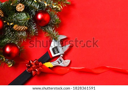 Christmas construction tools. Christmas presentation of construction. Construction theme. A set of wrenches and fir branches on a red background. Set of building tools. Advertising,card. Copy space.