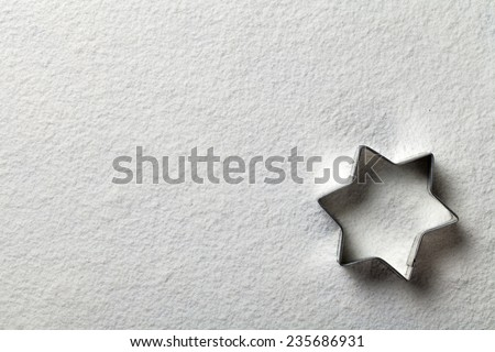 Christmas cookie mold in shape of star on flour background. Copy space. White flour looks like snow. Top view. Focus on mold edge