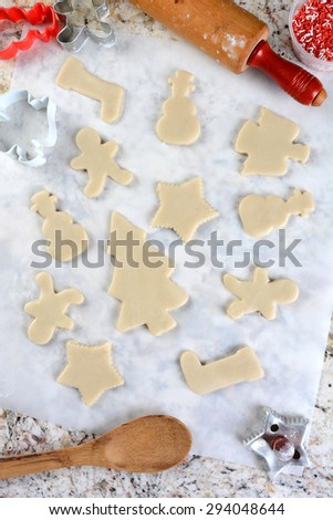 Christmas Cookie shapes on parchment paper. Around the perimeter are cutters, tub of sprinkles, spoon and rolling pin. Vertical format from a high angle.