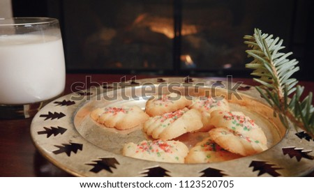 Stock Photo Christmas cookies and milk left out for santa claus in front of a fireplace. Fire flickers behind the traditional holiday baked goods put out for St. Nick on Christmas Eve.